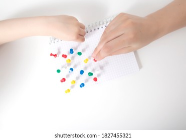 The hand of a child and a doctor sets multi-colored pins in a leaf on a white background. Autism development concept of a child thinking in games, autism, neurosonography