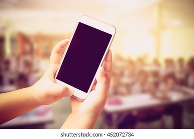 hand of child holding mobile phone with blur student learning in classroom background