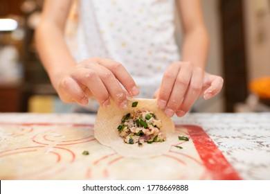 Hand of child making dumplings