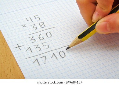 Hand of a child making a multiplication with a pencil. Math. School concept