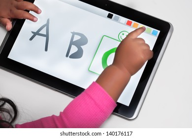 The hand of a child on a touchscreen tablet with educational software.