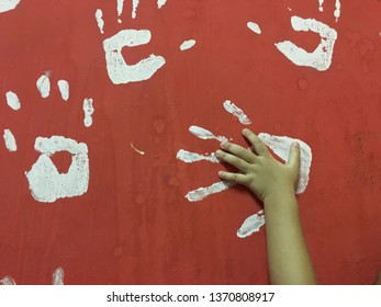Hand the child on a white hand print icon on the red wall.