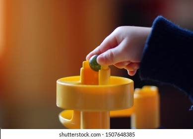 Hand of a child playing with a marble run
