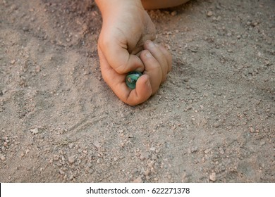 Hand of child playing marbles