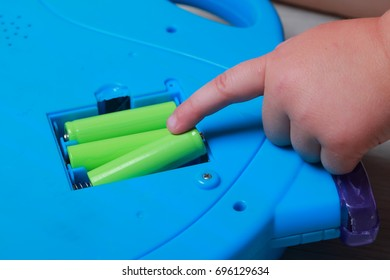hand the child put the batteries in the blue toy