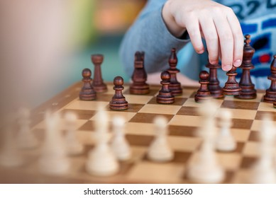 Hand of a child shifting a chessboard to a chess game.
