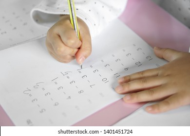 hand of child or student holding pencil and study with learning writing number and practice subtracting mathematics on paper book or homework in home or classroom at school or kindergarten and nursery