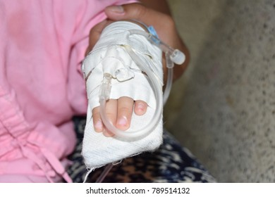 Hand of the child with a syringe into the blood vessels to fill the saline and medicine.