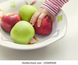 hand of child taking apple from bowl