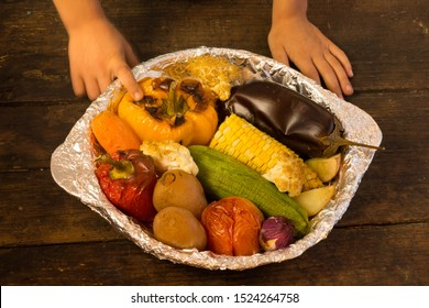 Hand of a child touching baked vegetables in foil potato carrot pepper onion corn on the cob eggplant cauliflower squash on wooden table