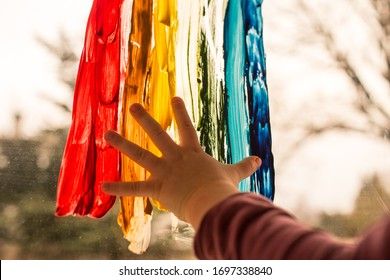 Hand of child touching colorful rainbow, painted on window, playtime during covid-19 pandemic. Concept of hope. Let's all be well. Social flash mob during self isolation and social distancing.