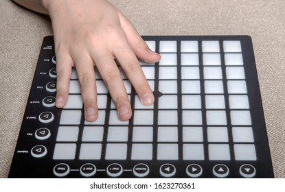 The hand of a child who plays on Launchpad. The MIDI controller that the child controls with his hand