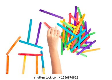 Hand of children is connecting the colorful popsicle sticks joyfully isolated on white background.