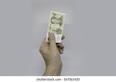 Hand with China Yuan currency note over white background