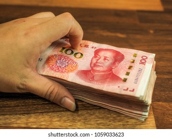 Hand with chinese one hundred Yuan banknotes