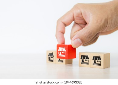 Hand choose cube wooden toy blocks stacked with franchise business store icon for growth and strategy of financial marketing planning and bank loan for branch expansion franchisee.