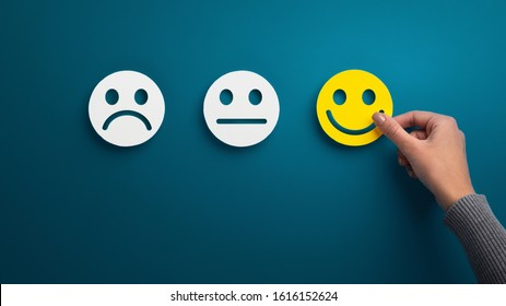 Hand choose the happy smile icon over blue background, panorama, copy space. Customer service evaluation and satisfaction survey concept