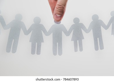 The hand chooses a man from among people. Paper figures are holding hands, employees, a crowd of people. Selection of people, recruitment, search for employees concept. Woman and man.