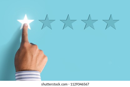Hand choosing 1 star rating on blue background - negative feedback concept