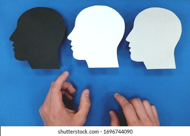 Hand choosing between three versions of self in human head silhouette. Personality and identity crisis concept.