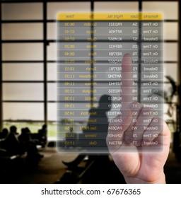hand choosing flights pushing a screen interface at the airport
