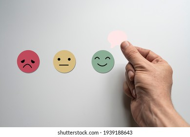 Hand choosing green happy smile face paper cut, feedback rating and positive customer review, experience, satisfaction survey ,mental health assessment, world mental health day concept