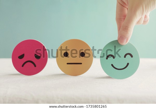 Hand choosing happy smile face paper cut, good feedback rating and positive customer review, experience, satisfaction survey ,mental health assessment, child wellness,world mental health day concept