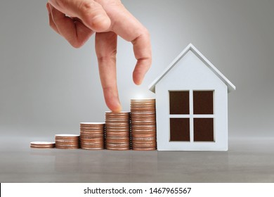 Hand choosing row of coin money house Planning to buy property