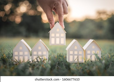 Hand choosing white paper house model from group of house on green grass, selective focus, Planning to buy property. Choose what's the best. A symbol for construction ,ecology, loan concepts