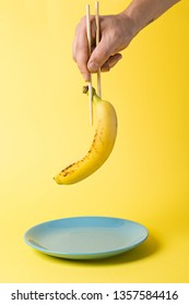 Hand with chopsticks holding a banana over a teal plate isolated on a yellow background