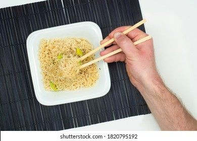 Hand with chopsticks picks up instant noodles from ceramic bowl on bamboo black mat and white background. Top view on cheap, low nutrition, fast food meal.