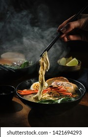 Hand with chopsticks takes noodles of ramen soup. Traditional Asian cuisine.