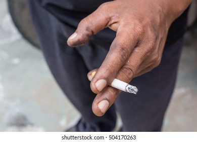 Hand with cigarette in outdoor closeup, Man smoking a cigarette.