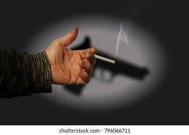 Hand with cigarette and the shadow of a pistol.