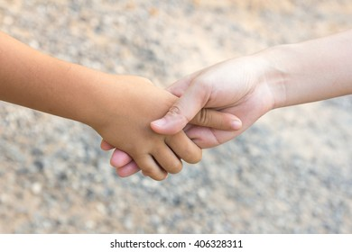 Hand clasp between child and adult