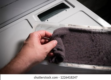 Hand cleaning accumulated clothing lint from trap in clothes dryer.