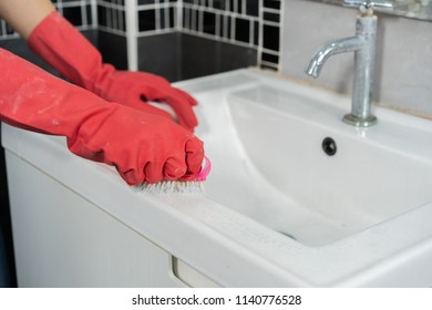hand cleaning bathroom sink with a brush
