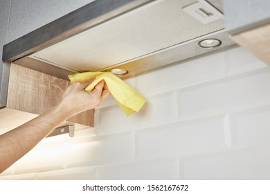 Hand cleaning kitchen hood with yellow washcloth