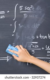 Hand cleaning mathematics formula on blackboard