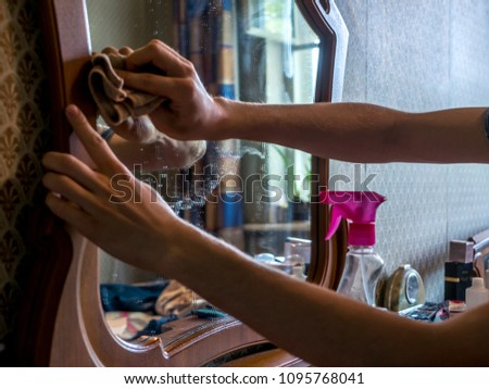 hand cleaning mirror with spray detergent at home