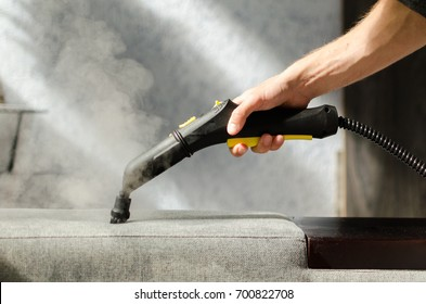 Hand cleaning sofa with a steam cleaner. Home cleaning concept.