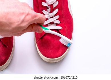 Hand cleans red shoes with a toothbrush. life hack for the care of suede