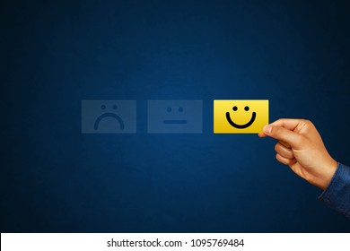 Hand of client show a feedback with smiley face card. Service rating, satisfaction concept