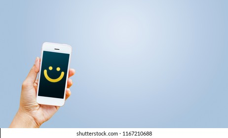 Hand of client show a feedback with smiley face card on smart phone. Service rating, satisfaction, customer experience concept
