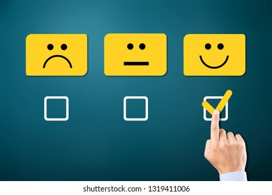 Hand of client show a feedback with smiling face card. Service rating, satisfaction concept          - Image