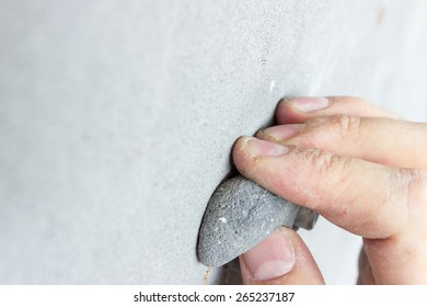 Hand of Climber Holding A Climbing Hold In A Climbing Gym