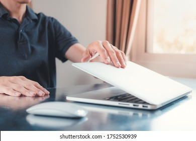 Hand close or open laptop on the table at home