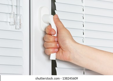 Hand closes white plastic the window with shutters