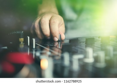 Hand of club party dj mixing music tracks with professinal sound mixer device. Disc jockey adjust cross fader knob to regulate track volume and cut songs in the mix. Bright green stage lights