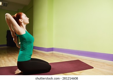 Hand clutched behind back yoga position profile view